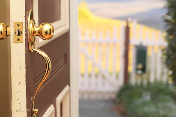 Opened Brown Front Door with Gold Hardware